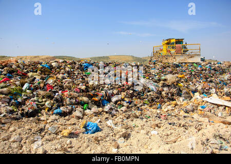 A bulldozer is arranging solid waste for a landfill site in Palestine - Stock Photo