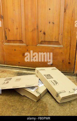 Amazon delivery boxes on the floor by the front door of house in England, UK - Stock Photo
