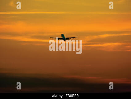 Passenger airplane flying above clouds in evening. real photo. - Stock Photo