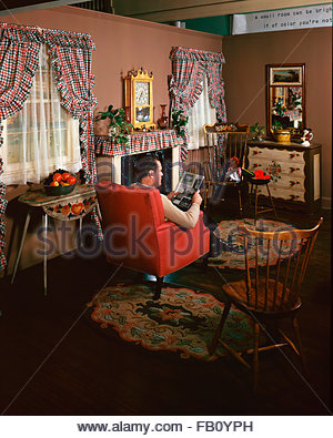 Furniture with model at Marshall Field and, 1943 Dec. 8. Living room with plaid curtains, man sitting in a chair - Stock Photo