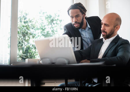 Two businessmen working with laptop by desk in office - Stock Photo