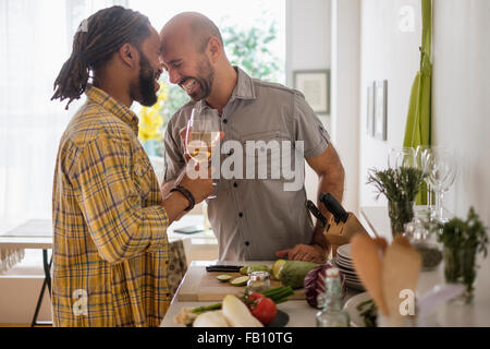 Smiley homosexual couple drinking wine in kitchen - Stock Photo