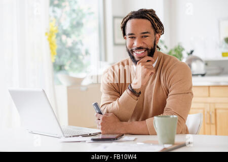Portrait of smiley young man with laptop at table - Stock Photo