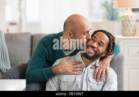 Homosexual couple kissing by sofa in living room - Stock Photo