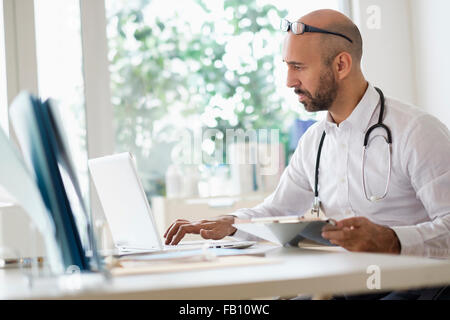 Concentrated doctor working with laptop at desk in office - Stock Photo