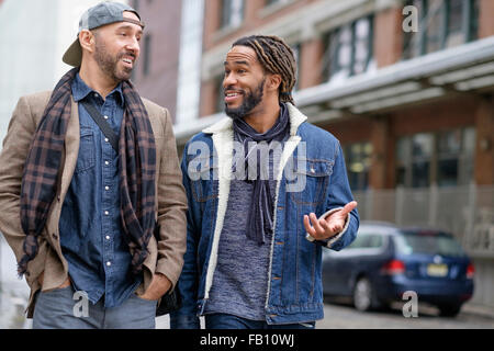 Smiley homosexual couple walking down street - Stock Photo