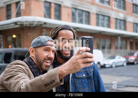 Smiley homosexual couple taking selfie with smart phone in street - Stock Photo