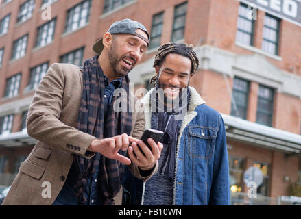 Smiley homosexual couple looking at smart phone in street - Stock Photo