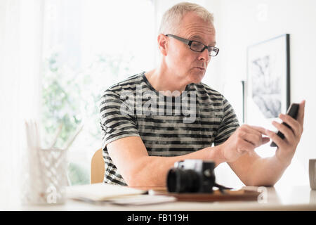 Man in home office using smartphone - Stock Photo