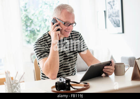 Man in home office using smartphone and tablet - Stock Photo