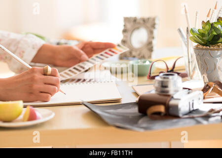 Young woman writing in note pad - Stock Photo