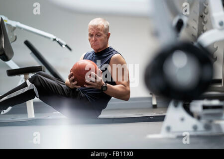 Man in health club exercising with ball - Stock Photo