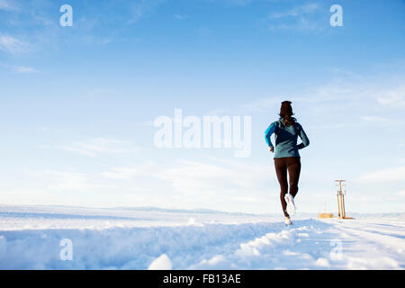Rear view of mature woman running in snow - Stock Photo
