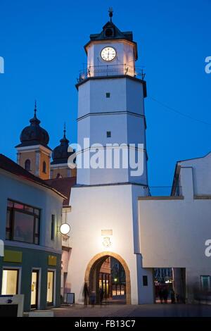 Illuminated clock tower at dusk - Stock Photo