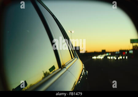 Sunset in city reflected in car's window - Stock Photo