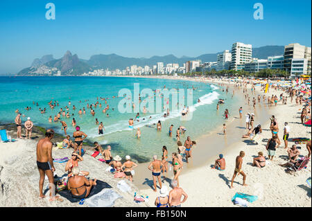 RIO DE JANEIRO, BRAZIL - FEBRUARY 08, 2015: Beachgoers take advantage of calm seas at the Arpoador end of Ipanema - Stock Photo