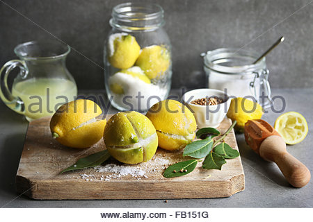 Preserved lemons with salt on a wooden board with a jar of lemon juice and spices on background - Stock Photo