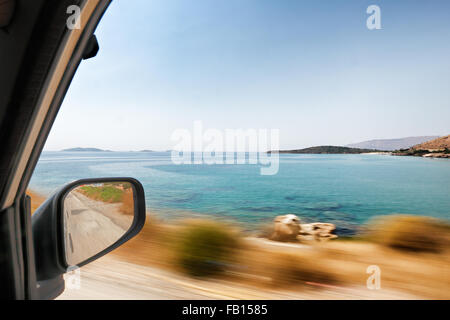 The view through the window from the perspective of the passenger in a moving car traveling around Andros, Greece - Stock Photo
