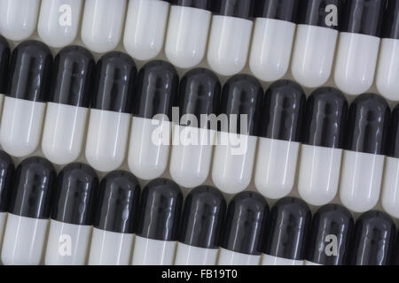 Close-up of pills - capsule form made of gelatin. Black / White pills. Metaphor Trump taking on American drug companies - Stock Photo