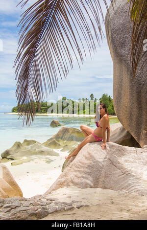 Beautiful woman posing on the famous Source D´Argent white sandy beach with palmtrees on September 27, 2015 in La - Stock Photo