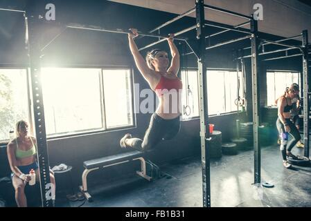 Woman swinging on exercise bar in gym - Stock Photo