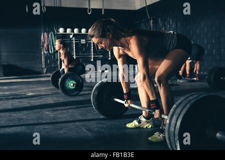 Women training with barbells in gym - Stock Photo