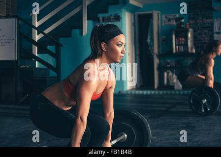 Woman crouching to lift barbell in gym - Stock Photo
