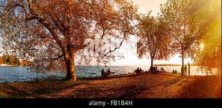 Panoramic view of tourists at sunlit lake Zug in autumn, Kanton of Zug, Switzerland - Stock Photo