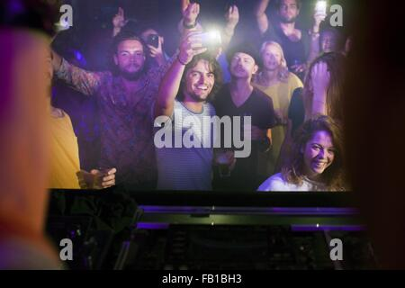 Group of friends watching and taking photograph of performer in club - Stock Photo
