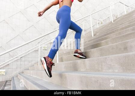 Low angle rear view of young woman, wearing sports clothing running up stairs - Stock Photo
