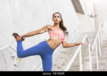 Low angle view of young woman holding ankle stretching leg, looking away - Stock Photo