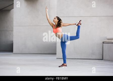 Side view of young woman balancing on one leg, leg raised holding ankle stretching - Stock Photo