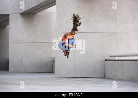 Side view of young woman jumping hugging knees in mid air - Stock Photo