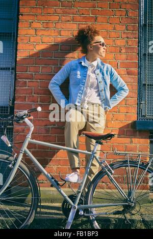 Young woman with bicycle wearing sunglasses leaning against brick wall, hands on hips looking away - Stock Photo