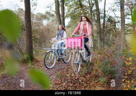 Teenage girls in forest cycling on bicycles with pink crate attached - Stock Photo