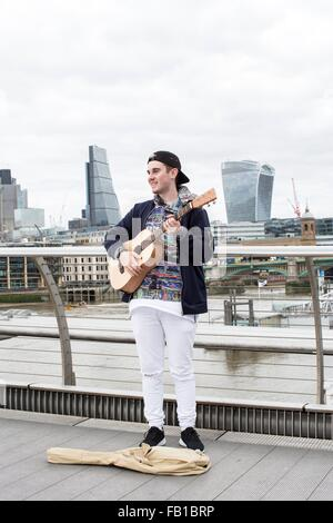 Young man busking on Millennium Bridge, London, UK - Stock Photo