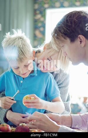 Parents and son peeling organic apples in kitchen - Stock Photo