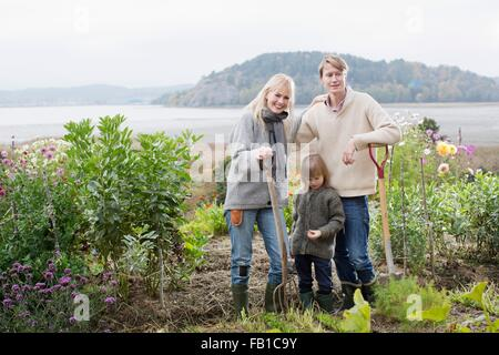Portrait of couple and son digging organic garden, Orust, Sweden - Stock Photo