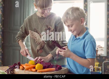 Mother and son preparing organic vegetables in kitchen - Stock Photo