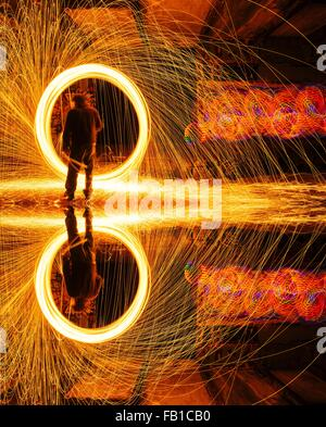 Mirror image of man creating circular golden spark light trails in derelict building - Stock Photo