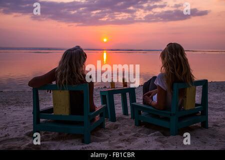 Silhouetted female tourists watching sunset over sea, Gili Trawangan, Lombok, Indonesia - Stock Photo