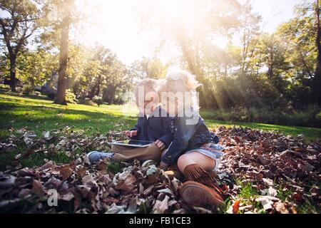 Children sitting on autumn leaf covered grass looking down using digital tablet - Stock Photo