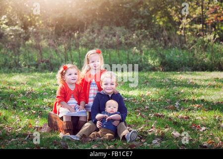 Four children family on autumn leaf covered grass posing for photograph smiling - Stock Photo