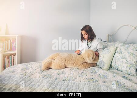 Girl dressed up in lab coat sitting in bed using stethoscope on soft toy - Stock Photo