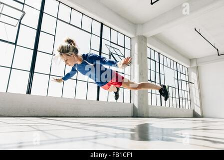 Low angle view of young woman in gym doing mid air push up - Stock Photo