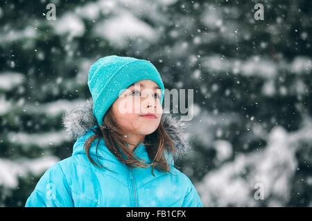Girl wearing knit hat looking away, snowing - Stock Photo