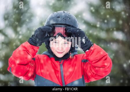 Boy wearing helmet and skiing goggles looking at camera smiling, snowing - Stock Photo