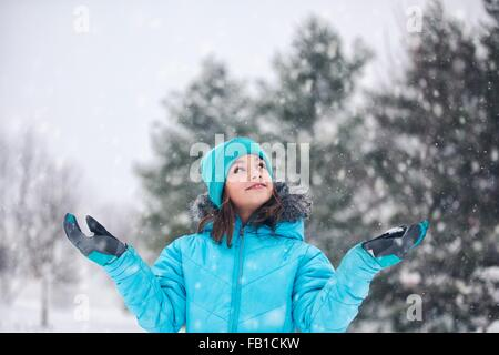 Girl wearing turquoise knit hat and coat, arms raised, hands out catching snow, looking up smiling - Stock Photo