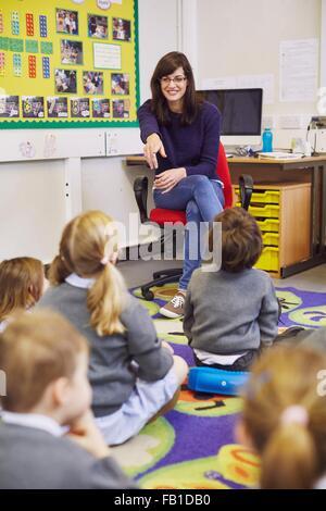 Teacher pointing to children sitting on floor in elementary school classroom - Stock Photo