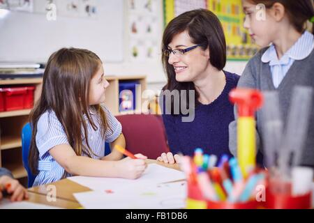 Girls drawing at desks in elementary school classroom - Stock Photo